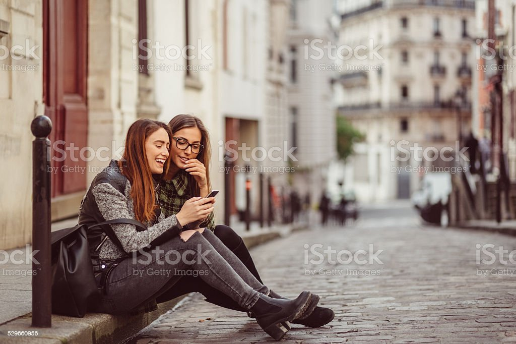 Girls in the city texting on smartphone stock photo