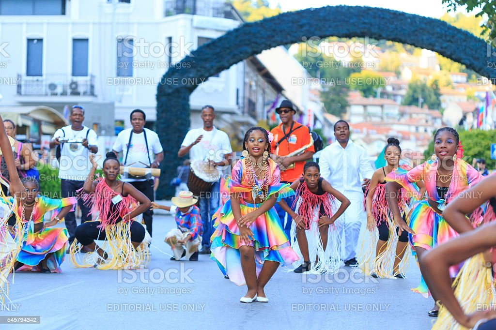Girls in traditional costumes dancing in front of musicians stock photo