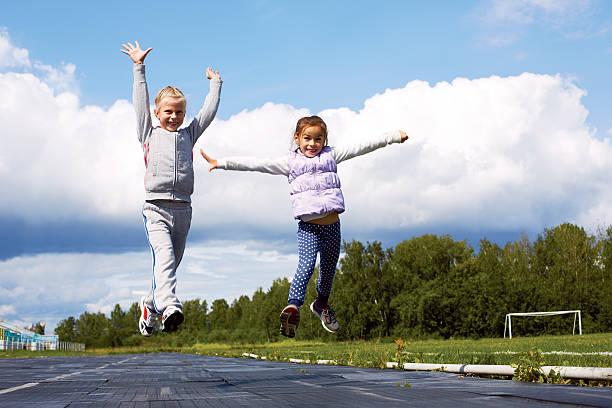 girls jumping in the stadium stock photo