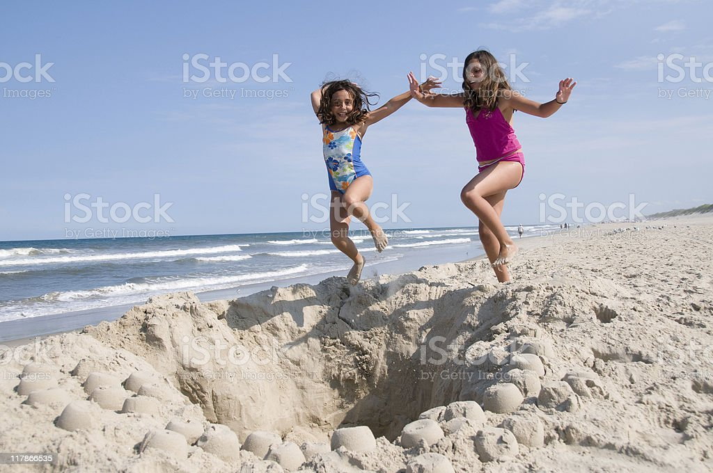 Girls Jumping into a Hole stock photo
