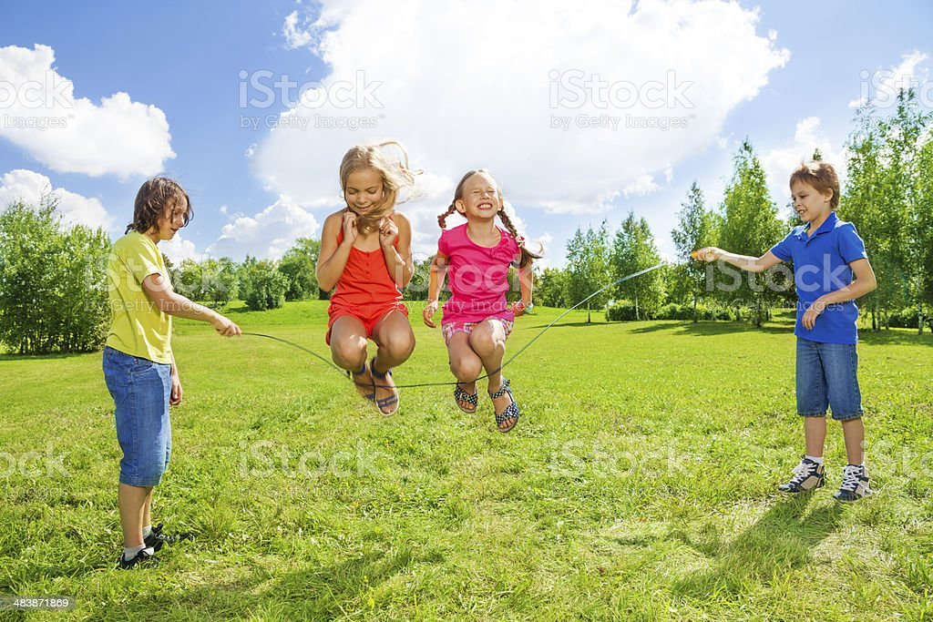 Girls jumping over the rope with friends stock photo
