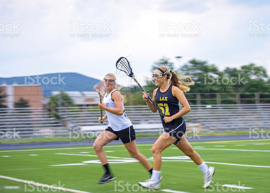Girls Lacrosse Players Sprint Down Field Towards Ball stock photo