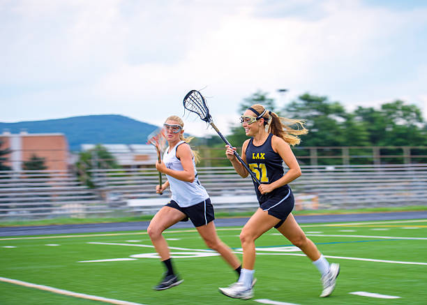 Girls Lacrosse Players Sprint Down Field Towards Ball Panning blur featured as two female La Crosse players from opposing teams race down the field. High degree of motion conveyed. Some motion blur on athletes, particular in extremeties, focus on face of closest player. protective eyewear stock pictures, royalty-free photos & images