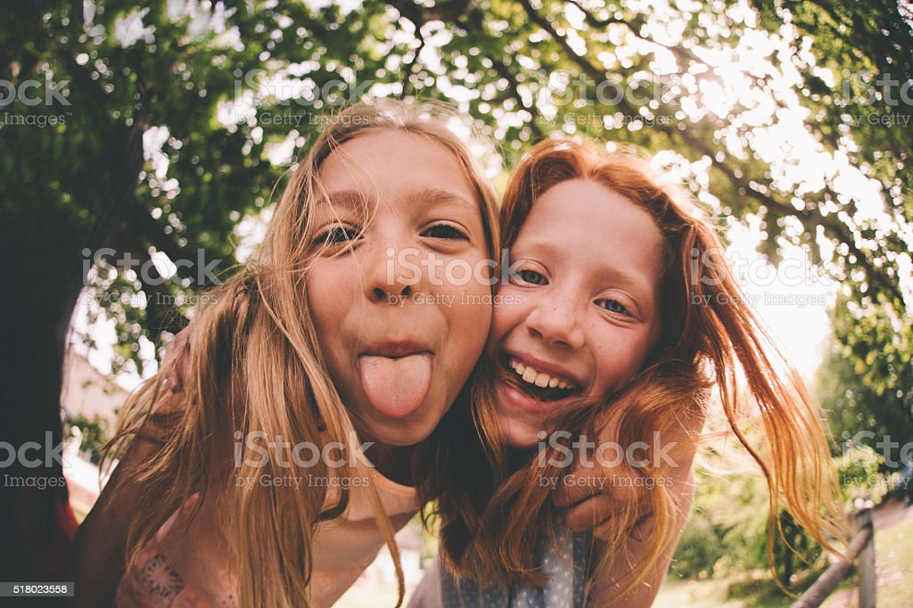 Girls laughing and pulling faces at the camera in park stock photo