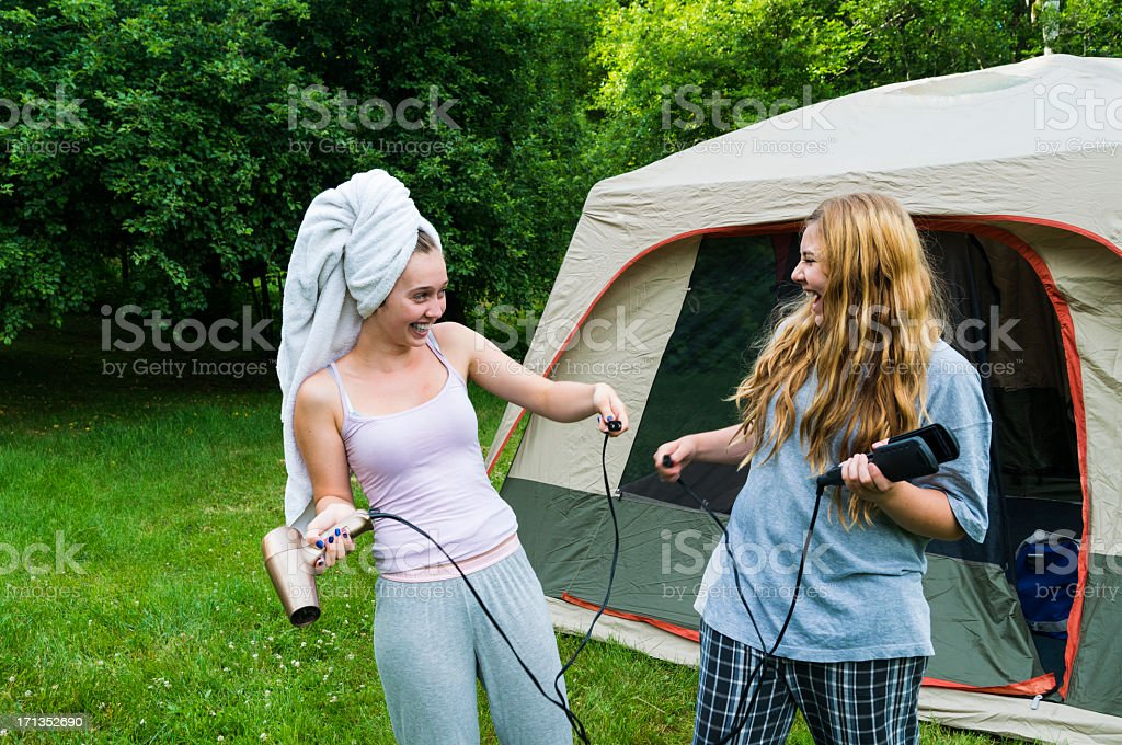 Girls laughing because there is no power outlet in camping. stock photo