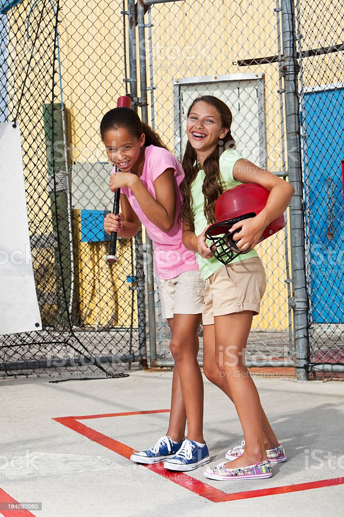 Girls laughing in batting cage royalty-free stock photo
