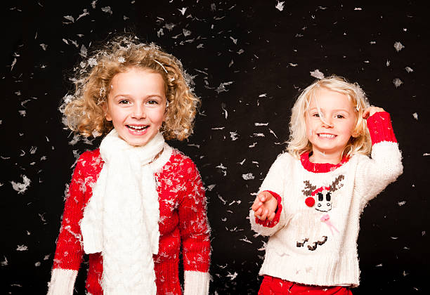 mädchen lachen in fallenden schnee - kinder weihnachtsfilme stock-fotos und bilder