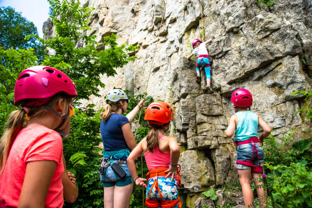Girls learning to climb from a female rock climbing instructor outside on a cliff face stock photo