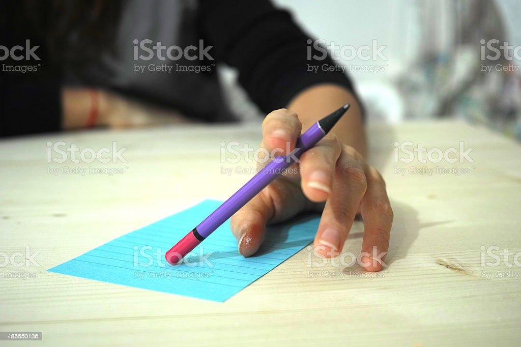 Girls Left Hand Holding a Pencil Like Waiting For Answers stock photo