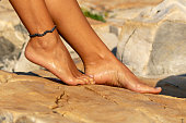 Girl's legs on a rocky beach in camping Baldarin in Cres, Croatia