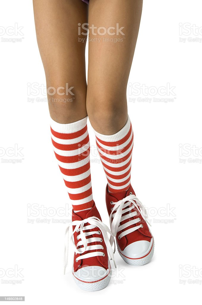 Girls legs wearing socks with red shoes. Clipping path included. stock photo