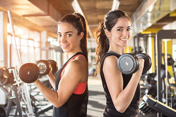 girls lifting weights in gym. - ウエイトトレーニング ストックフォトと画像