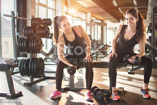 istock Girls lifting weights in gym. 635742918