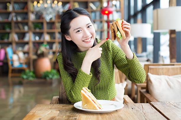 mädchen essen sandwich, - hamburger makkaroni stock-fotos und bilder