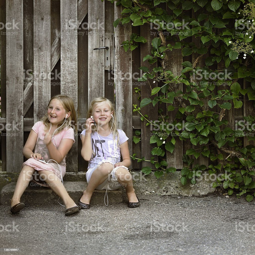 Girls listening to mp3 players together stock photo