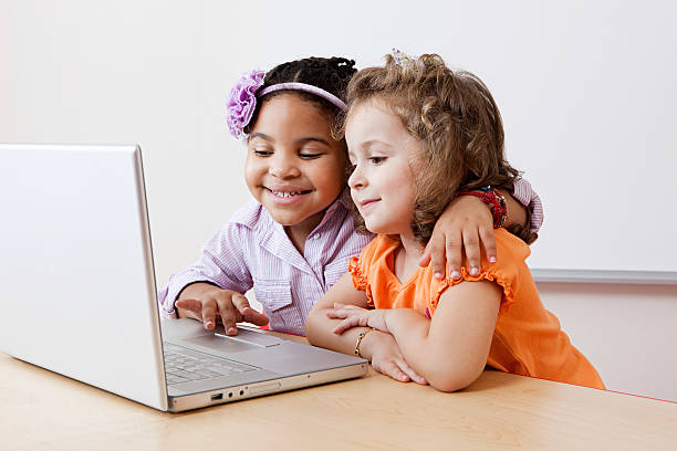 Girls looking at laptop together stock photo
