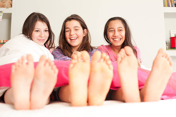 girls lying in bed laughing stock photo