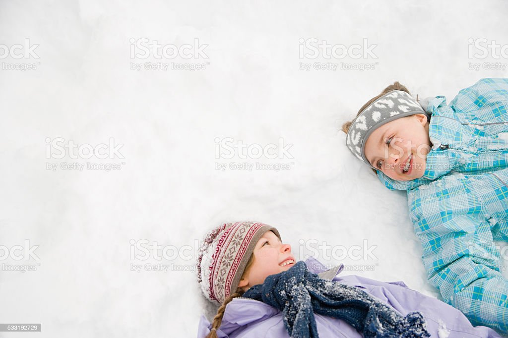 Girls lying in snow stock photo