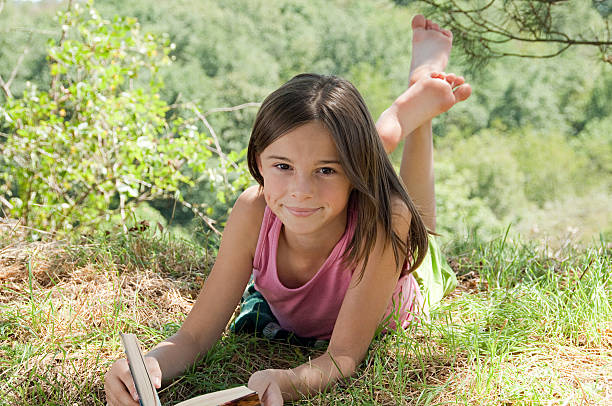 ragazze prono con libro - bambine femmine foto e immagini stock