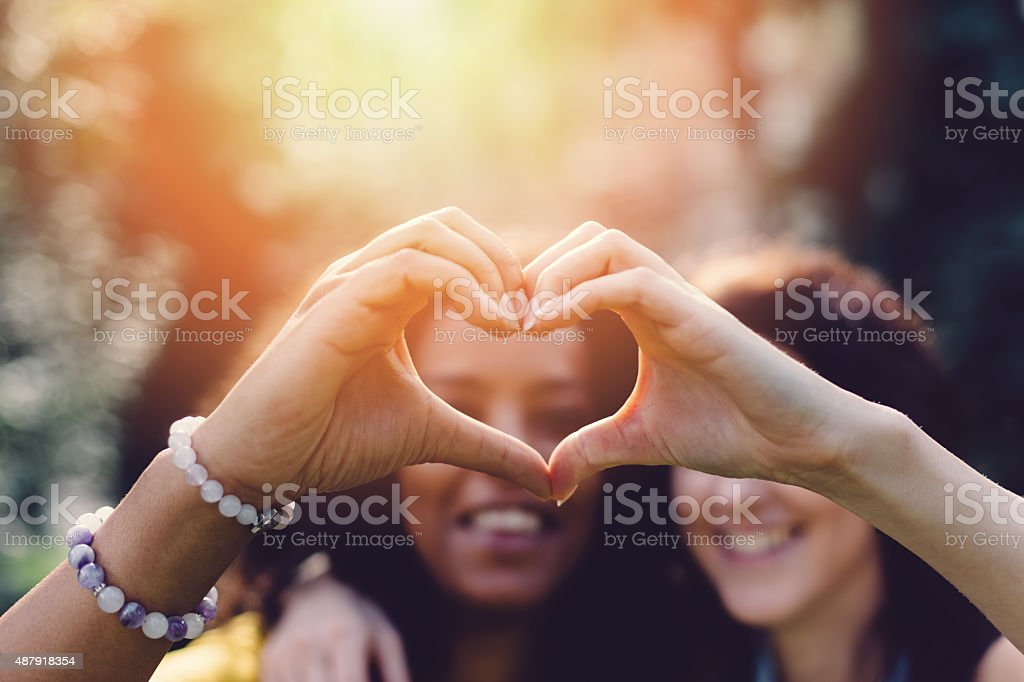 Girls making heart with hands stock photo