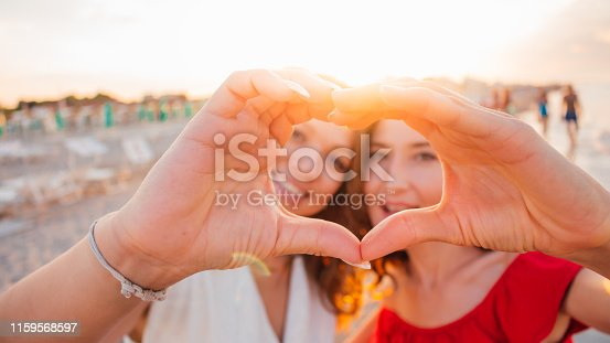 Two smiling girls (young women) making selfie on the beach with sunshine background.