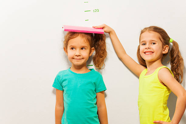 girls measure height on wall scale - height measurement stock photos and pictures