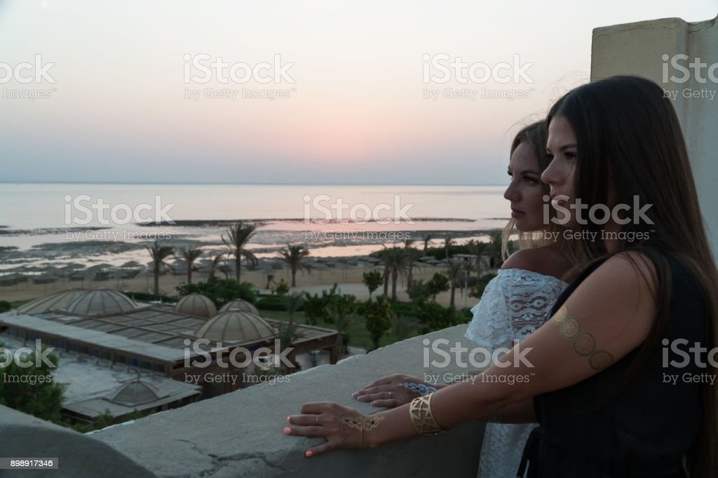 Girls meet the dawn on the roof of the building stock photo