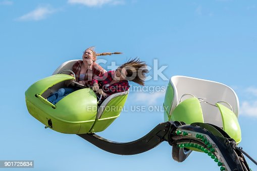 Saint John, New Brunswick, Canada - September 2, 2017: At the Saint John Exhibition. Two girls with their hair flying on a fast rise, another ride car is empty.