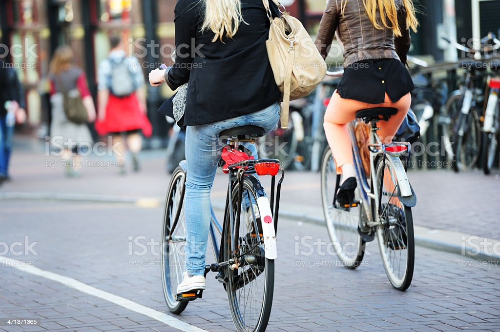 Girls on bicycles in traffic royalty-free stock photo