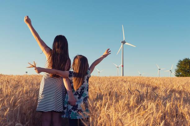filles sur le champ de céréales sont imitant des éoliennes - concept d'énergie éolienne - nuage 6 photos et images de collection