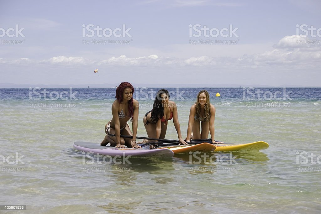 Girls on paddle Boards at Beach stock photo