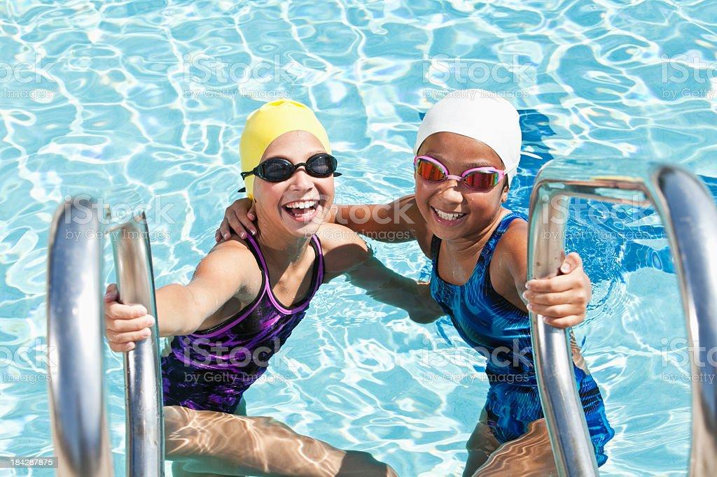 Girls on swimming pool ladder stock photo
