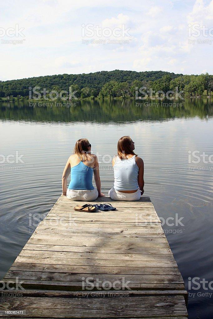 Girls on the Dock overlooking Lake royalty-free stock photo
