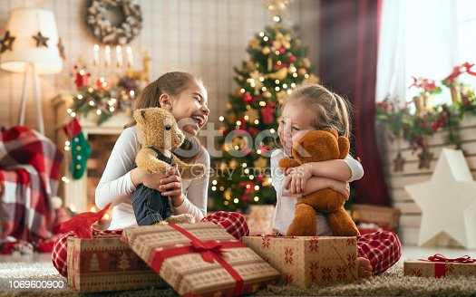 istock girls opening Christmas gifts 1069600900