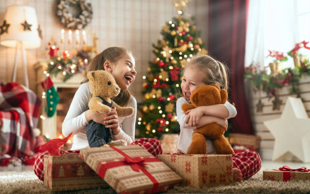girls opening christmas gifts - toy stock pictures, royalty-free photos & images