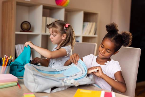 Girls packing school bags stock photo