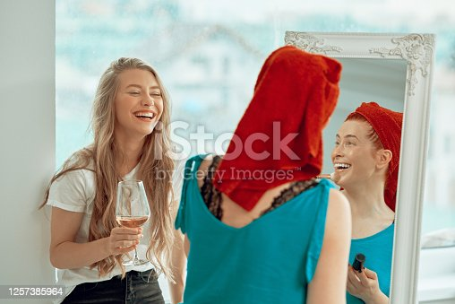 Blond girl laughing holding glass of wine together with redhead putting on makeup