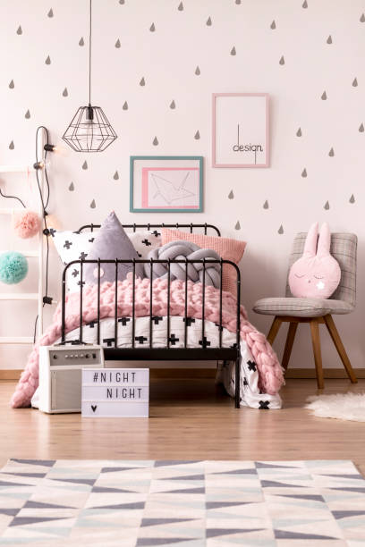 Girl's pastel bedroom interior Pink knit blanket on girl's bed against the wall with posters in pastel bedroom interior with chair girl bedroom stock pictures, royalty-free photos & images