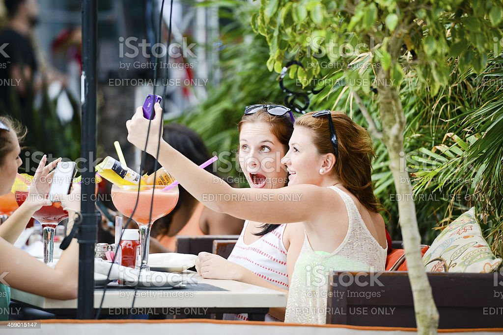 Girls photographing themselves with mobile phones royalty-free stock photo