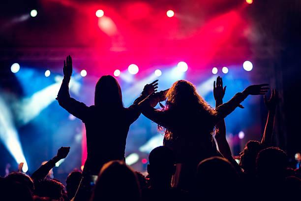 Girls piggyback riding at a concert - Photo