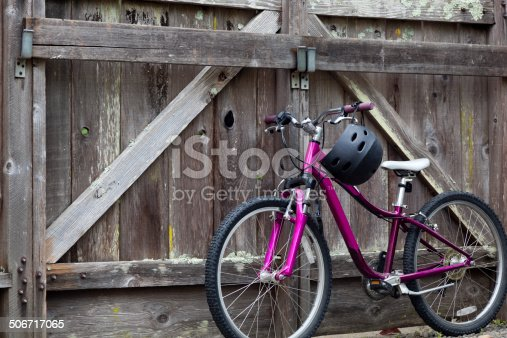 girl's pink bicycle leaning against wood fence