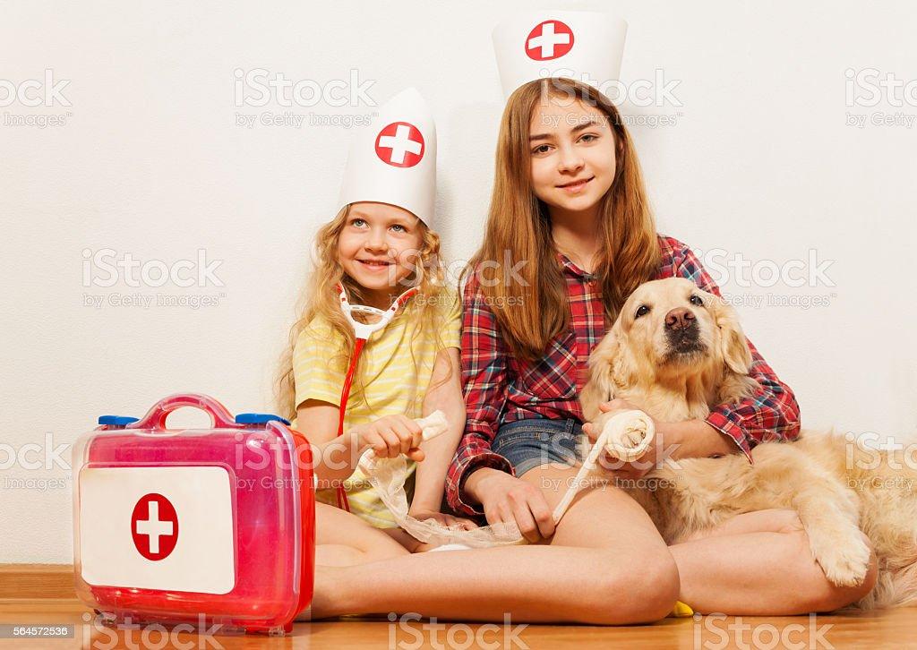 Girls play cute doctors bandaging their pet dog stock photo