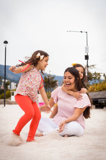 Girls play with their mom stock photo