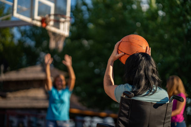 jeunes filles jouant au basket-ball avec les femmes sur un fauteuil roulant - sports en fauteuil roulant photos et images de collection