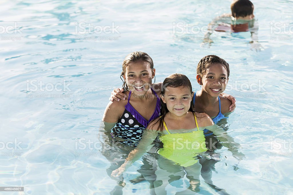 Girls playing in swimming pool. stock photo