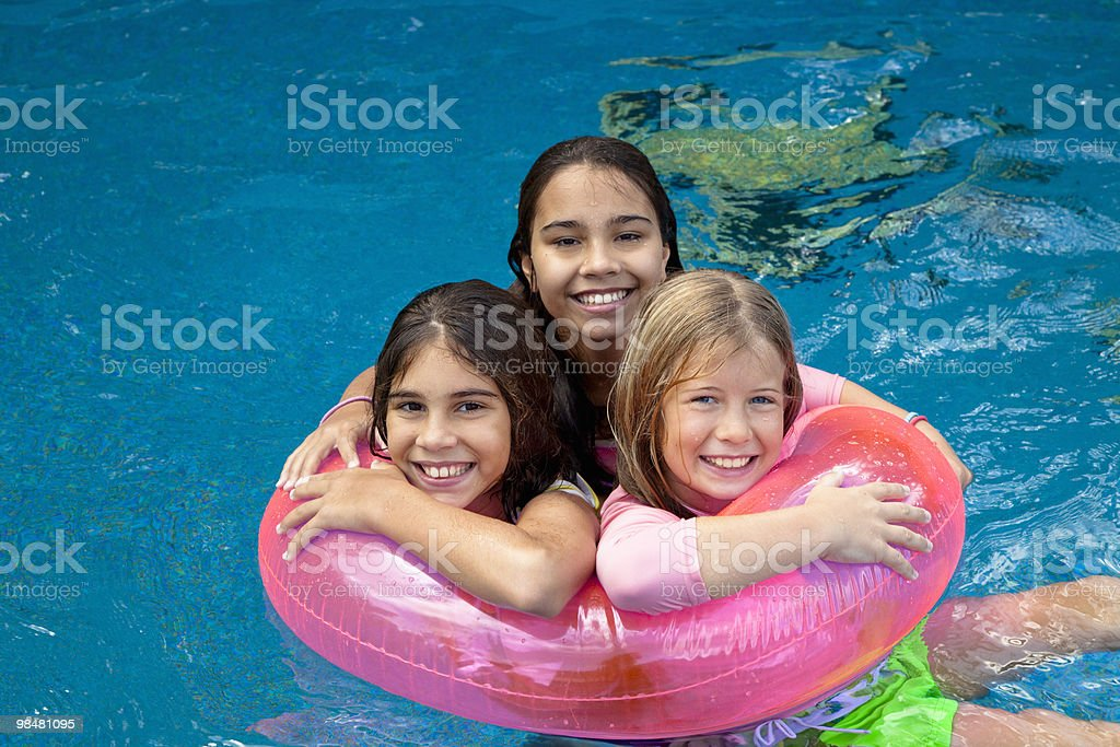 Girls playing in swimming pool with intertube royalty-free stock photo