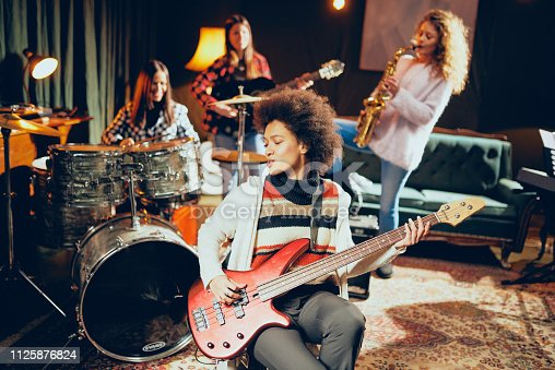 Girls playing jazz music. In foreground one woman playing bass guitar and in background other three playing acoustic guitar, saxophone and drums. Home studio interior.