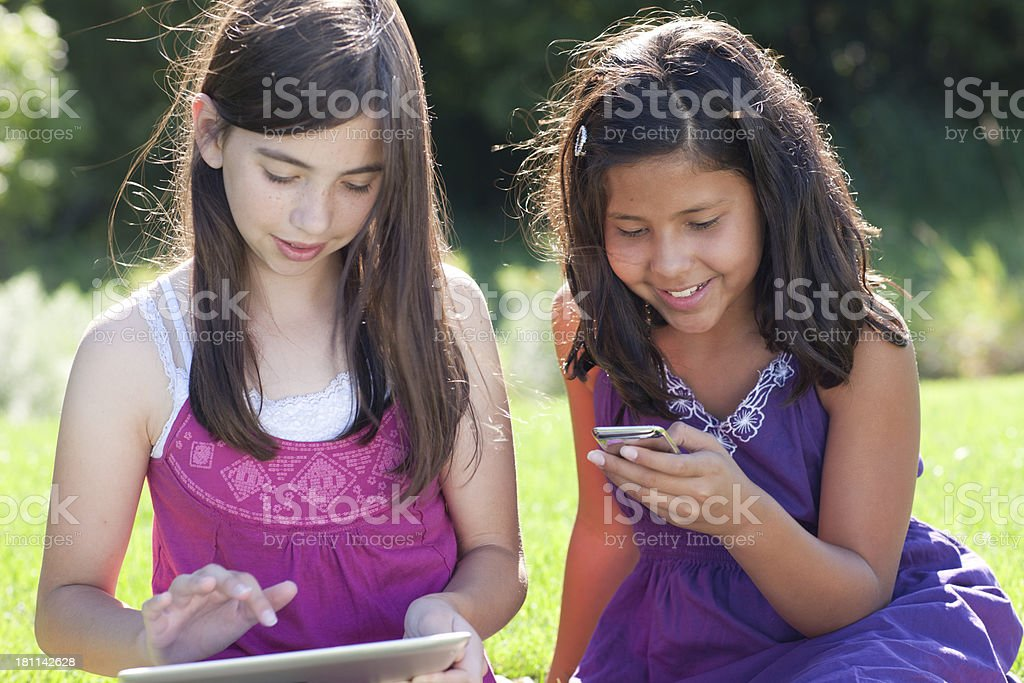 Girls Playing MP3 player and Digital Tablet royalty-free stock photo