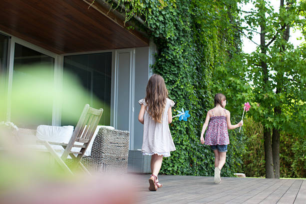 girls playing on patio with pinwheels - focus on background stock photos and pictures