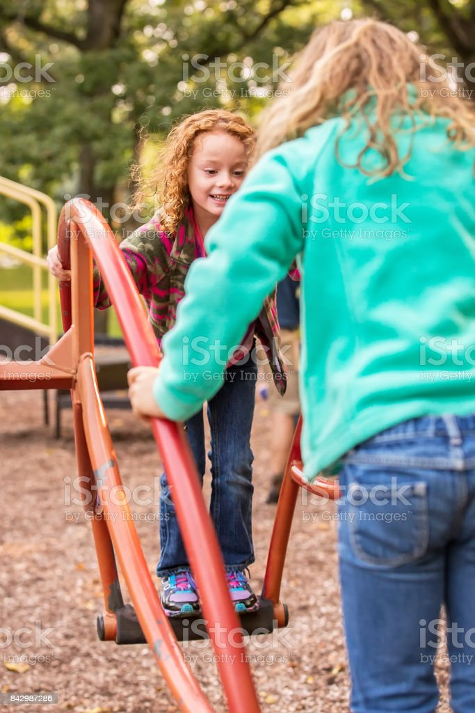 Girls Playing on Teeter Totter At Park in Autumn stock photo